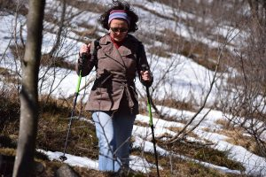 une femme pratiquant la marche nordique dans les bois
