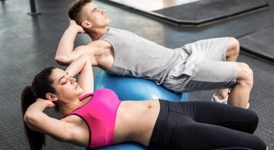 Fit couple doing abdominal crunches on fitness ball at crossfit gym